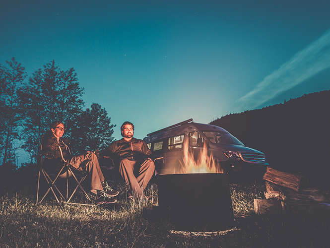 Young couple sitting around a campfire