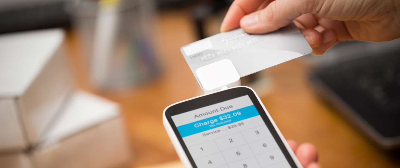 Image of customer swiping card on smartphone using card reader