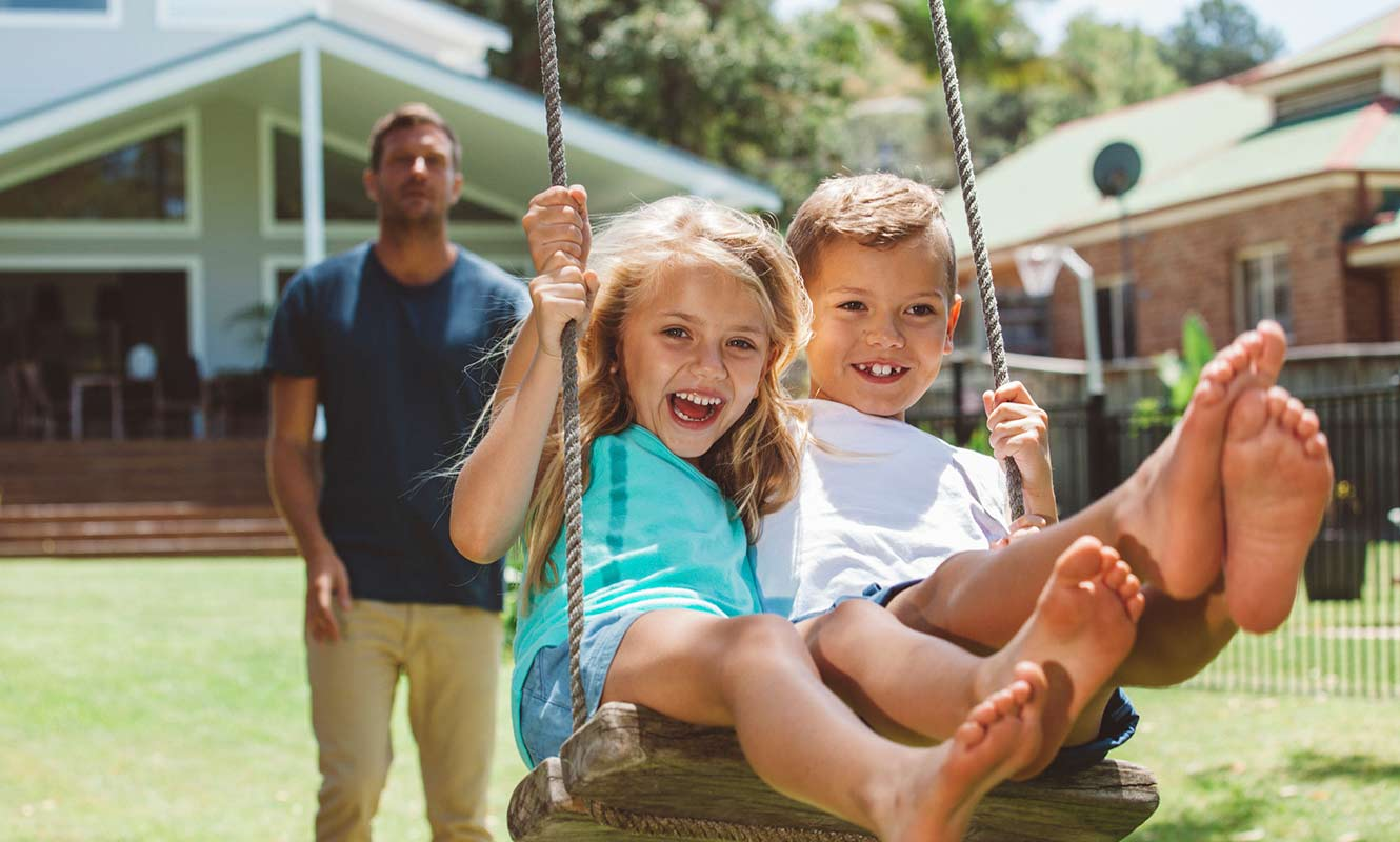 Father pushing son and daughter on swing in yard; Hero Image Mortgage