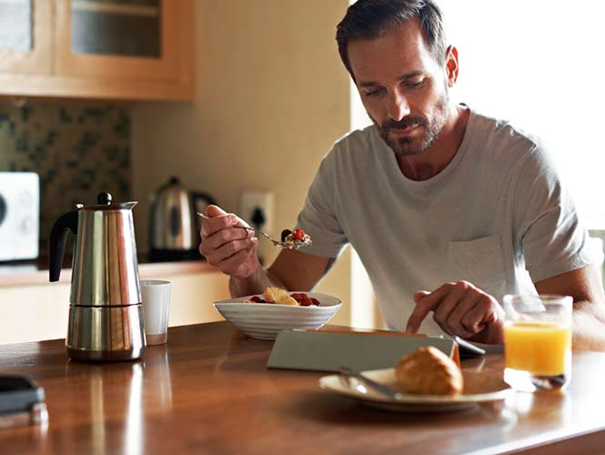 Image of a man eating breakfast at kitchen table and using tablet