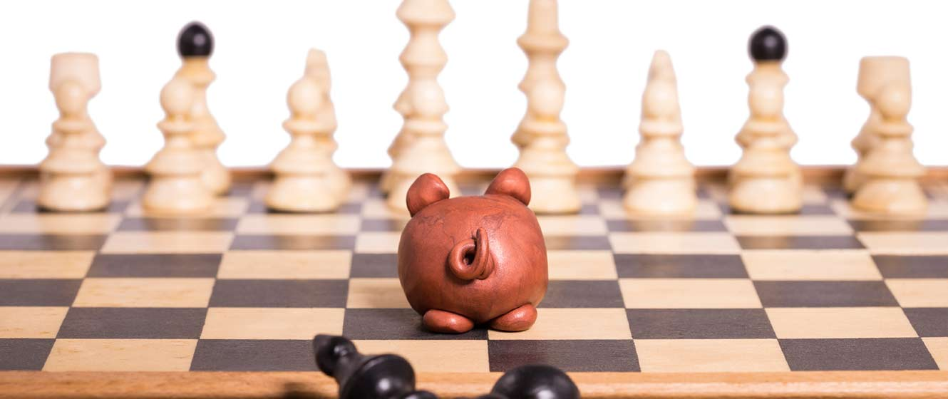 Image of chess set with piggy bank