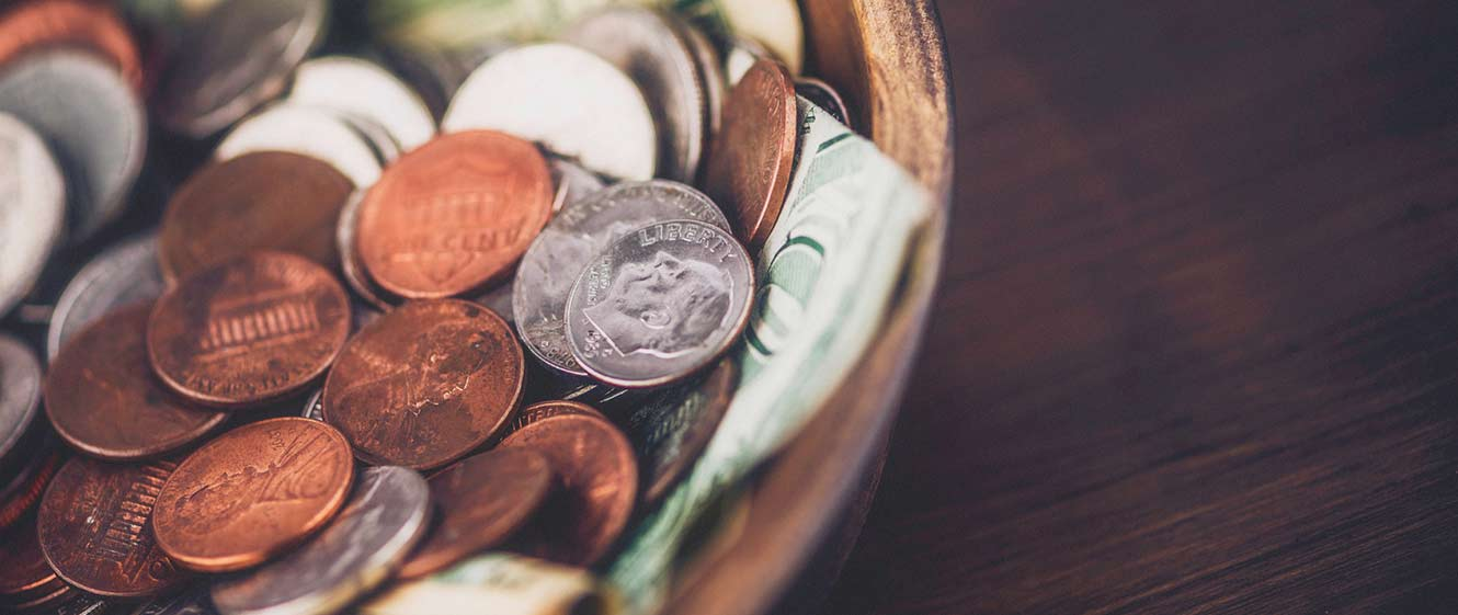 Image of coins with currency notes in a bowl.