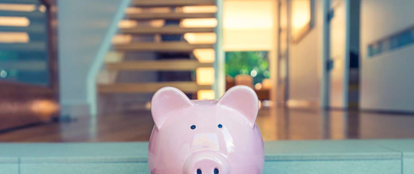 Image of piggy bank in front of house interior.