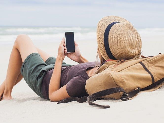 Woman using her mobile banking app at the beach