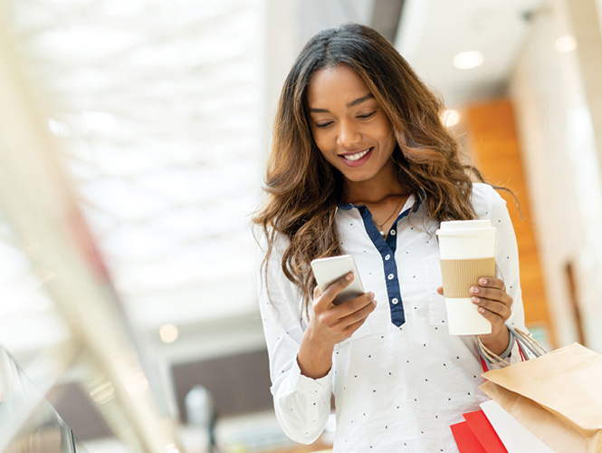 Young woman checking her phone while shopping