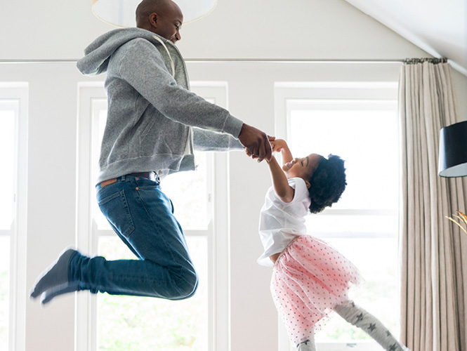 Father and daughter holding hands jumping in a room.
